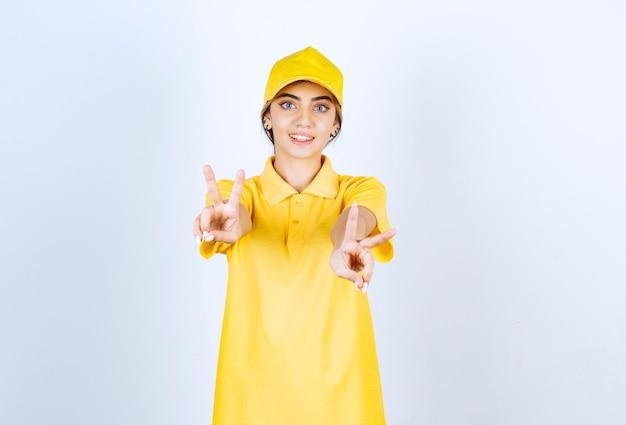 Donna delle consegne in uniforme gialla in piedi e che mostra il segno della vittoria.