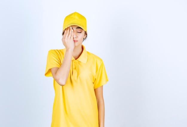 Donna delle consegne in uniforme gialla in piedi con la faccia assonnata e gli occhi chiusi.