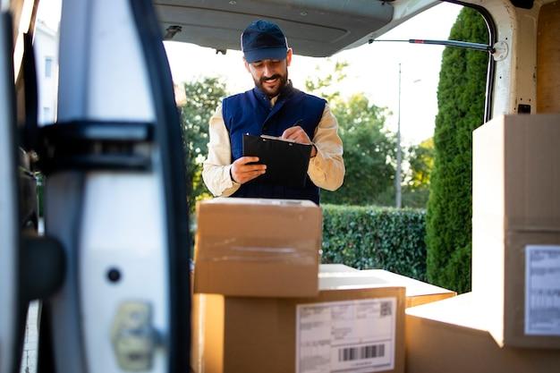 Работник службы доставки проверяет посылки перед доставкой на место.