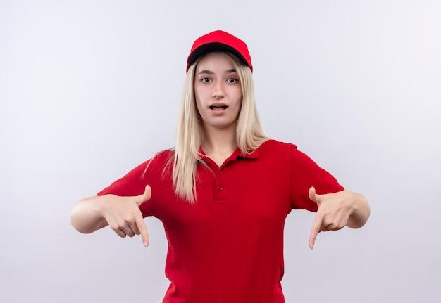 Молодая девушка из службы доставки в красной футболке и кепке указывает вниз на изолированную белую стену