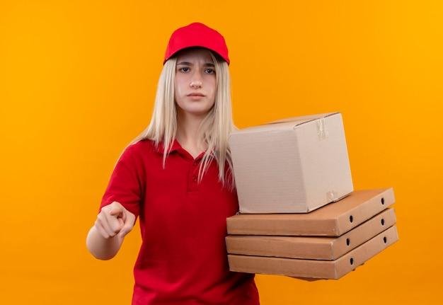孤立したオレンジ色の壁にジェスチャーを示す赤いtシャツとキャップ保持ボックスを身に着けている配達若い女性