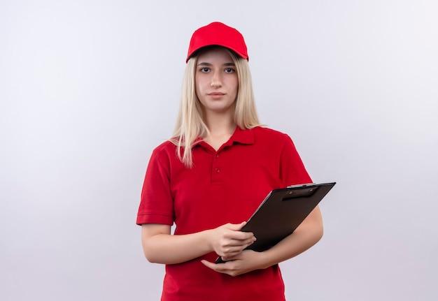 孤立した白い壁にクリップボードを保持している赤いtシャツと帽子を身に着けている若い女性