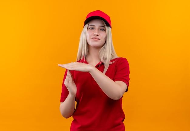 Молодая женщина доставки в красной футболке и кепке показывает жест тайм-аута на изолированной оранжевой стене