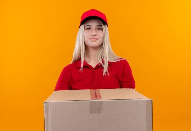Consegna giovane donna che indossa t-shirt rossa e cappuccio che tiene grande scatola sulla parete arancione isolata