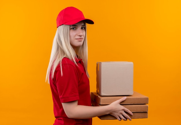 Consegna giovane donna che indossa t-shirt rossa e berretto tenendo le scatole a lato sulla parete arancione isolata