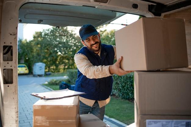 Доставщик собирает посылки в своем фургоне перед доставкой.