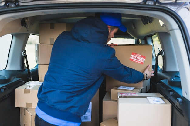 Deliveryman in car with carton boxes