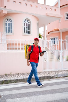 배달원 횡단 도로 및 노란색 열 가방을 들고. 발에 순서를 제공하는 손에 태블릿으로 집중된 백인 택배.
