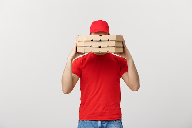 A deliveryman hidden behind a large stack of pizza boxes he is carrying.