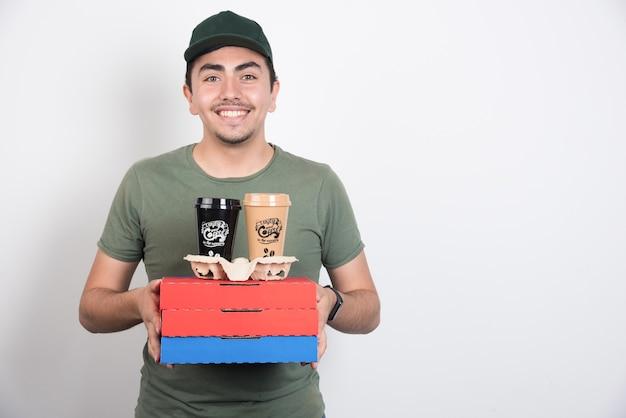 白い背景にピザとコーヒーの3つの箱を持っている配達員。