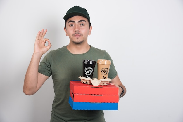Deliveryman holding three boxes of pizza and coffees on white background.