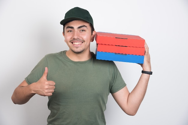 Deliveryman holding three boxes of pizza and showing thumbs up on white background.