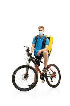 白いスタジオの背景に分離された自転車とフェイスマスクの配達員。検疫中の非接触サービス。男は隔離中に食べ物を届けます。安全性。専門職。広告のコピースペース。