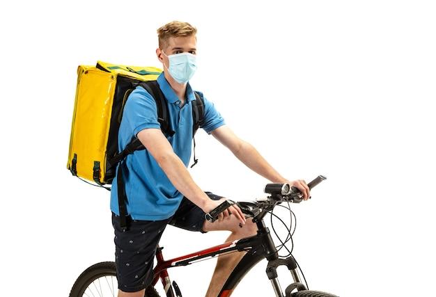 Доставщик в лицевой маске с велосипедом, изолированные на белом фоне студии. бесконтактное обслуживание во время карантина. человек разносит еду во время изоляции. безопасность. профессиональное занятие. copyspace для рекламы.