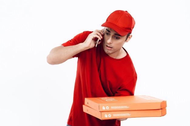オレンジ色の制服を着た配達員が電話に話しかけます。