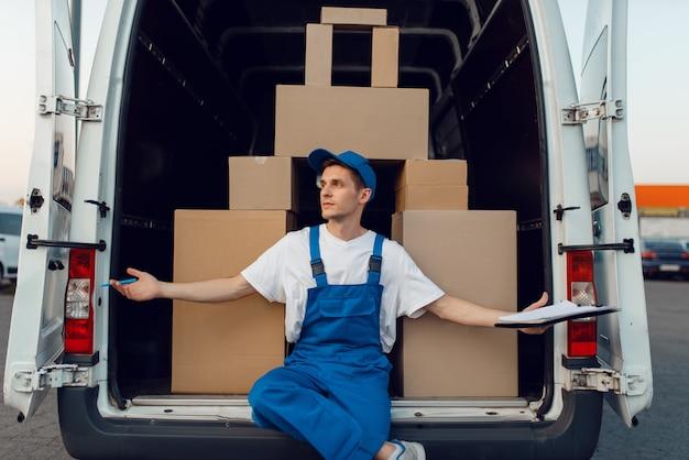 Экспедитор в форме у машины, ящики уложены пирамидально, служба доставки. человек, стоящий у картонных пакетов в автомобиле, доставка мужчин, курьер или доставка