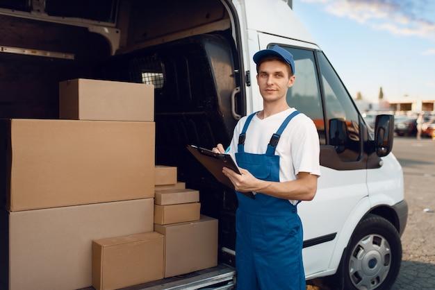Экспедитор в форме, картонные коробки в машине, служба доставки.
