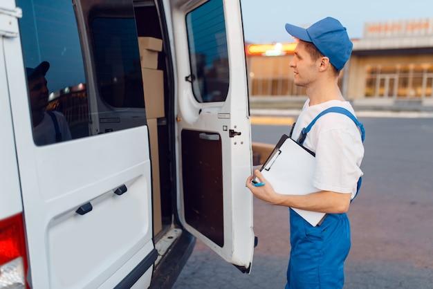 Экспедитор в форменной одежде, закрывание машины, служба доставки, доставка.
