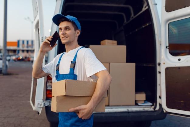 Доставщик в униформе держит посылку и мобильный телефон у машины, служба доставки
