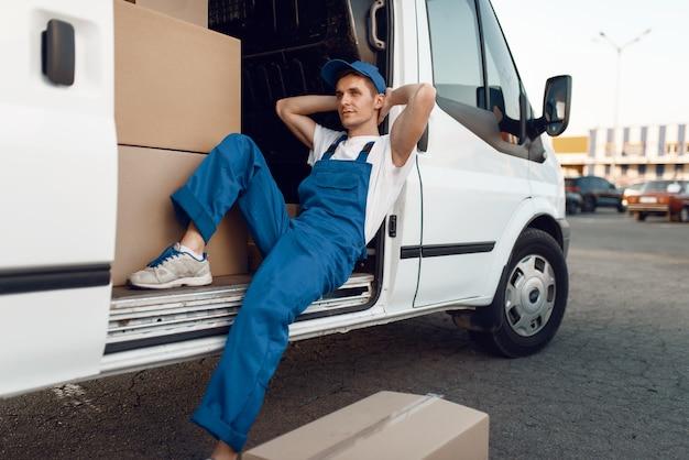 Экспедитор в форме отдыхает в машине во время перерыва, авто с посылками и картонными коробками, служба доставки. мужчина позирует на картонных упаковках в автомобиле, доставка мужчин, курьер или доставка