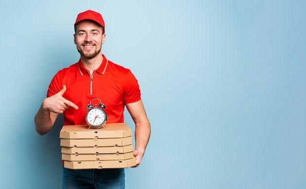 配達員はピザをすばやく配達するために時間厳守です。シアンの背景