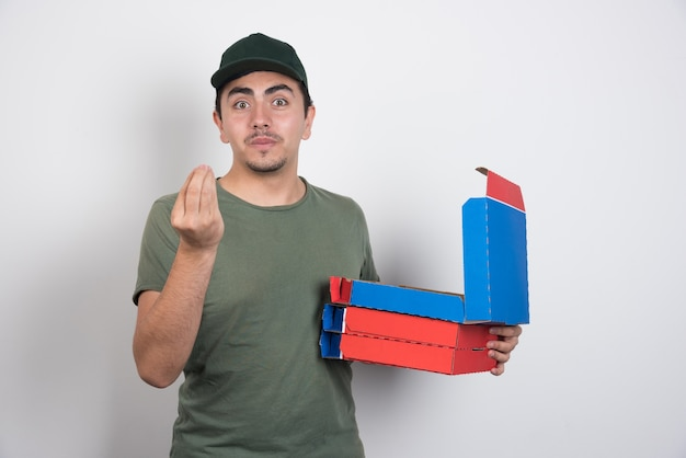 Deliveryman making hand sign and holding pizza boxes on white background.