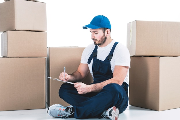 Deliveryman making notes near parcels