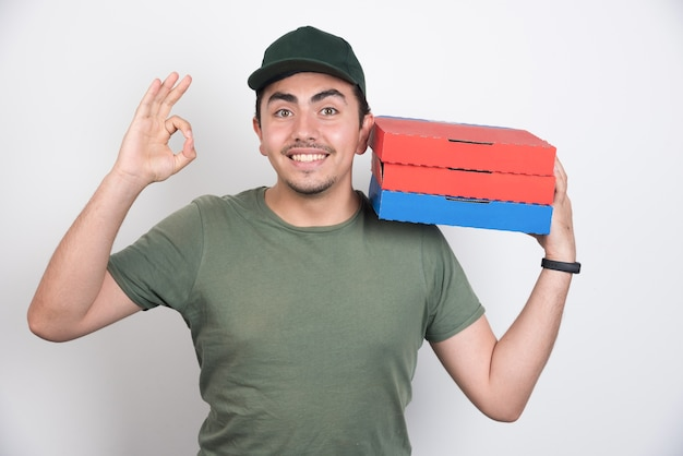 配達員はokのサインを作り、白い背景にピザの箱を持っています。