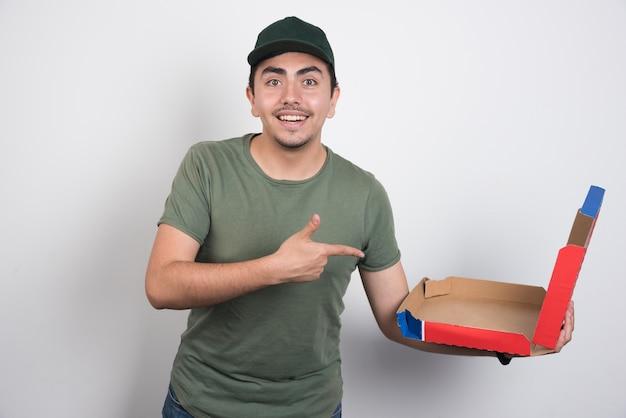 白い背景の上の空のピザボックスを指している配達員。