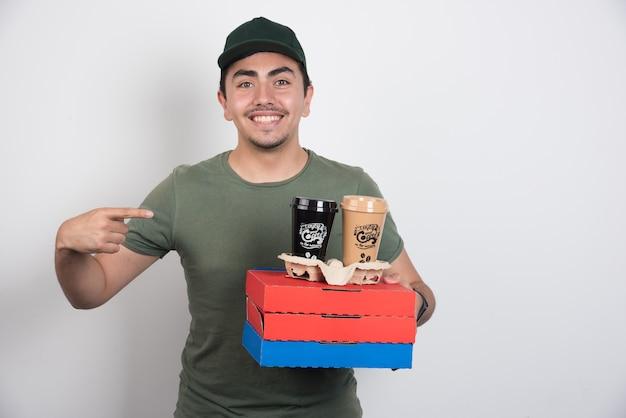 白い背景の上のピザとコーヒーの3つのボックスを指している配達員。