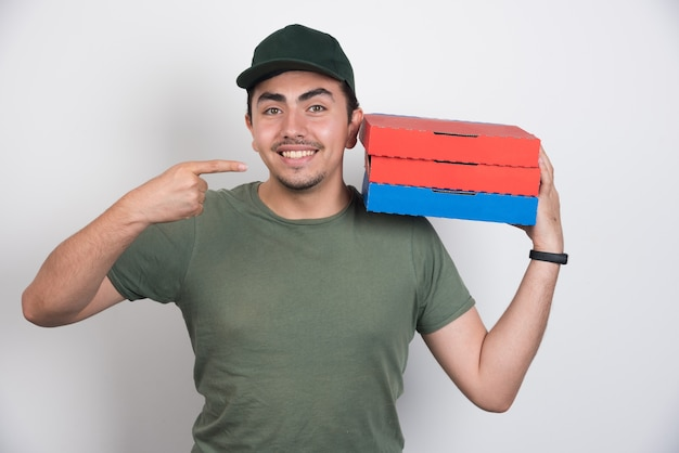 Deliveryman pointing at three boxes of pizza on white background.