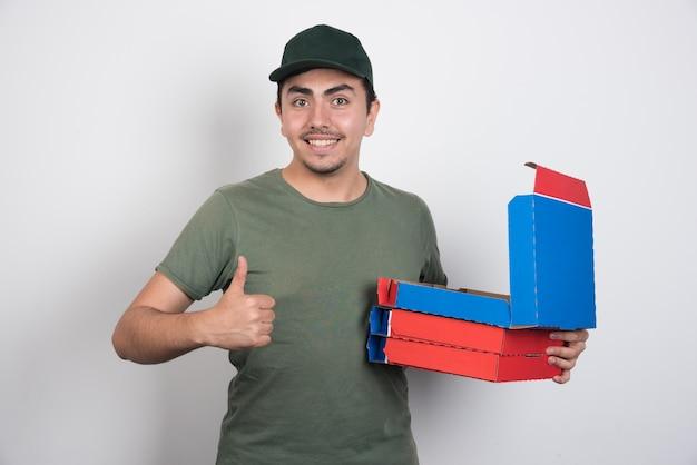 親指を立てて白い背景にピザの箱を運ぶ配達員。