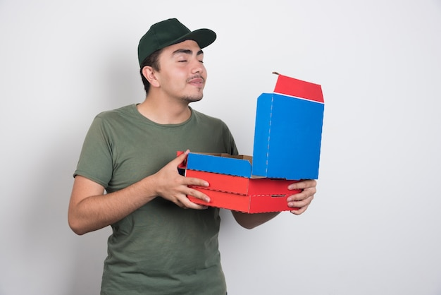 Deliveryman smelling pizza on white background.