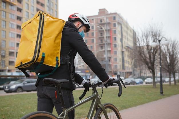 코로나 바이러스가 유행하는 동안 도시에서 자전거와 함께 걷고있는 열 배낭을 착용 한 배달원