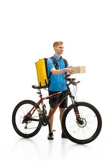 白いスタジオの背景に分離された自転車を持つ配達員。検疫中の非接触サービス。男は隔離中に食べ物を届けます。安全性。専門職。広告のコピースペース。