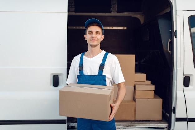 Экспедитор с картонной коробкой у машины, служба доставки. мужчина в униформе держит картонную упаковку, мужчина доставляет, курьерская работа