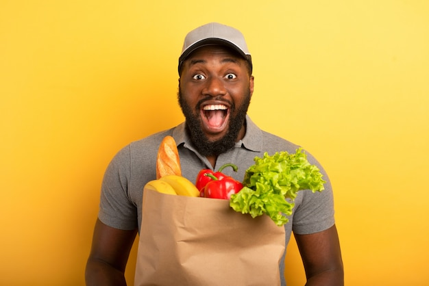 Deliveryman with happy expression ready to deliver bag with food. yellow wall.