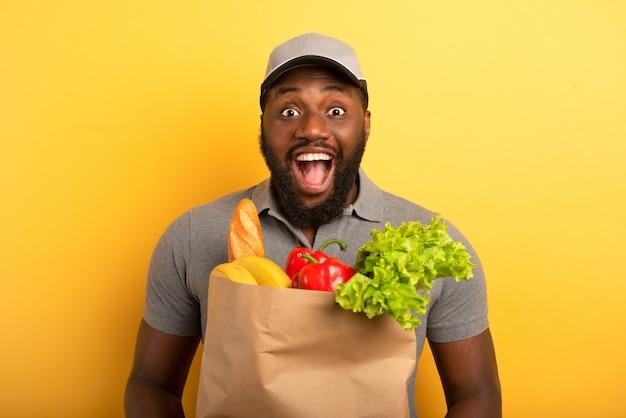 食べ物と一緒にバッグを配達する準備ができている幸せな表情の配達員。黄色い壁。