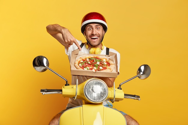 Deliveryman with helmet driving yellow scooter while holding pizza box