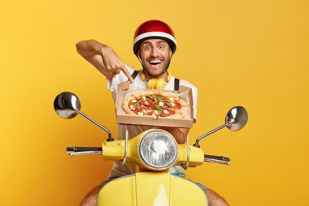 Fattorino con casco guida scooter giallo mentre si tiene la scatola della pizza