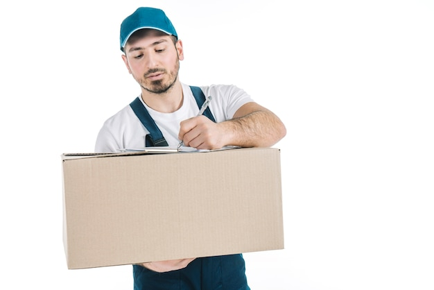 Deliveryman with parcel writing on clipboard