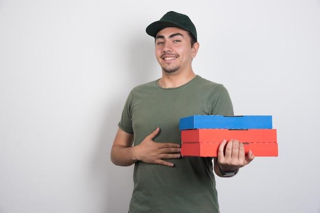 白い背景に彼の胃を保持しているピザの箱を持つ配達員。