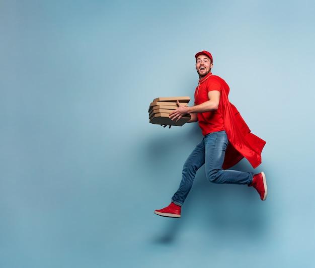 ピザを持った配達員は強力なスーパーヒーローのように振る舞います。出荷の成功と保証の概念。スタジオシアンの背景