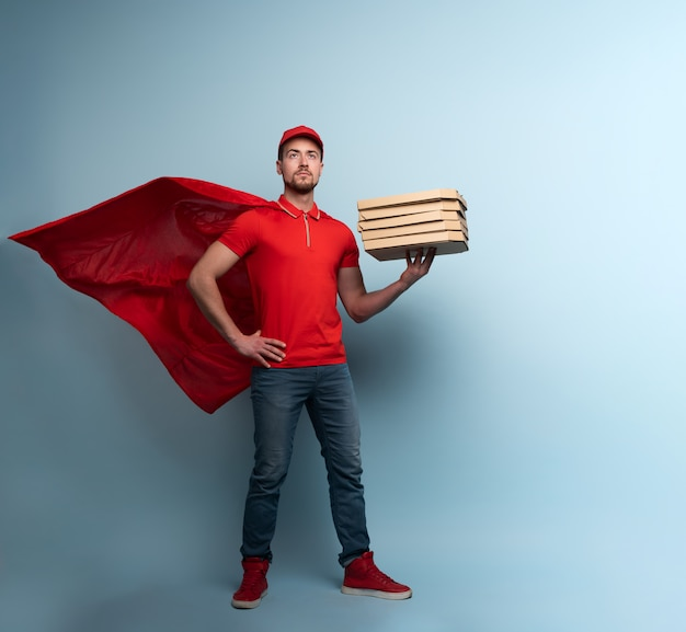 Deliveryman with pizzas acts like a powerful superhero. concept of success and guarantee on shipment. cyan background