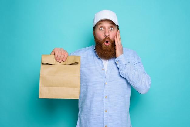 不思議な表情の配達員が、食べ物の入ったバッグを配達する準備ができています。シアンの背景。