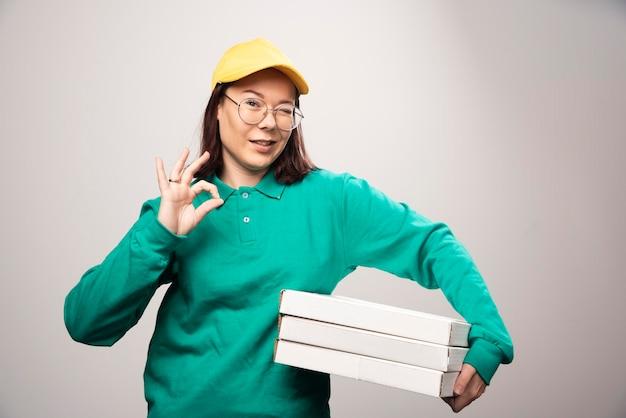 白のピザの段ボールを運ぶ配達員。高品質の写真