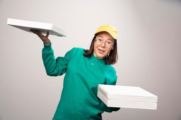 Доставщик, несущие картоны пиццы на белом. фото высокого качества