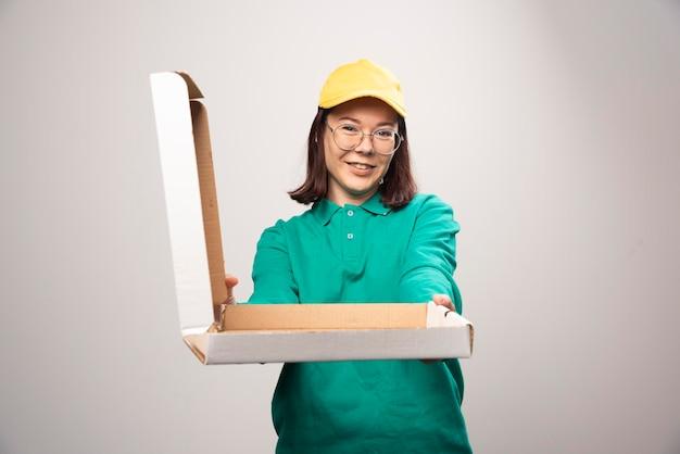 Fattorino che dà un cartone di pizza su un bianco. foto di alta qualità