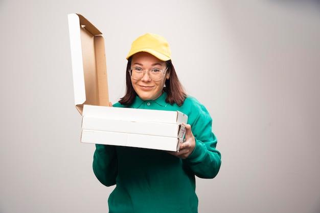 Доставщик, держа картоны пиццы на белом. фото высокого качества