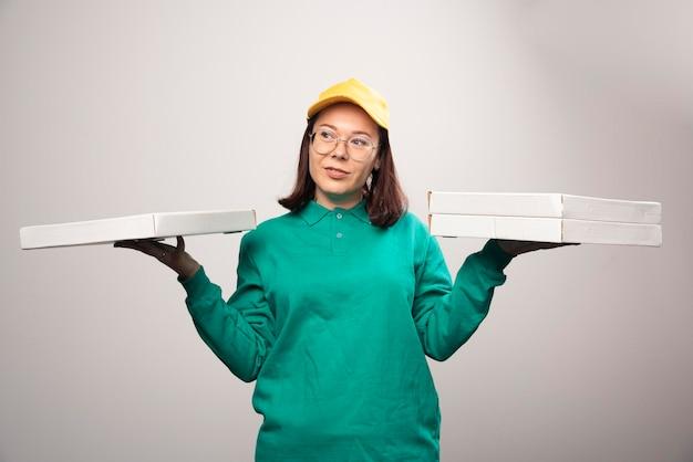 Fattorino che tiene cartoni di pizza su un bianco. foto di alta qualità